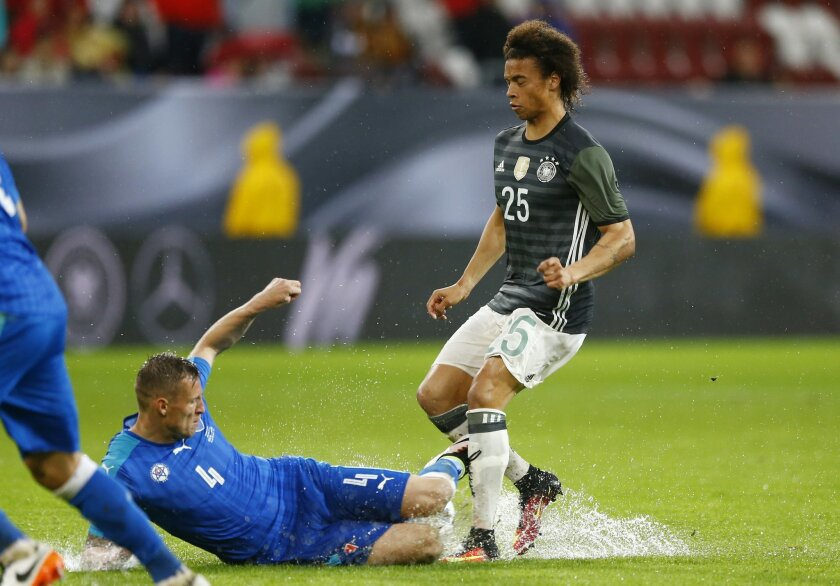 Slovakia's Jan Durica, left, and Germany's Leroy Sane challenge for the ball during a friendly soccer match between Germany and Slovakia in Augsburg, Germany,  Sunday, May 29, 2016. (AP Photo/Matthias Schrader)
