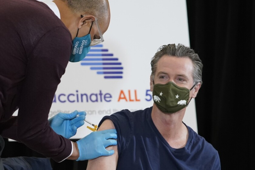 Dr. Mark Ghaly, Secretary, California Health and Human Services, left, inoculates California Gov. Gavin Newsom, right, at the Baldwin Hills Crenshaw Plaza in Los Angeles Thursday, April 1, 2021. Newsom was vaccinated with the new one-dose Janssen COVID-19 vaccine by Johnson & Johnson. (AP Photo/Damian Dovarganes)