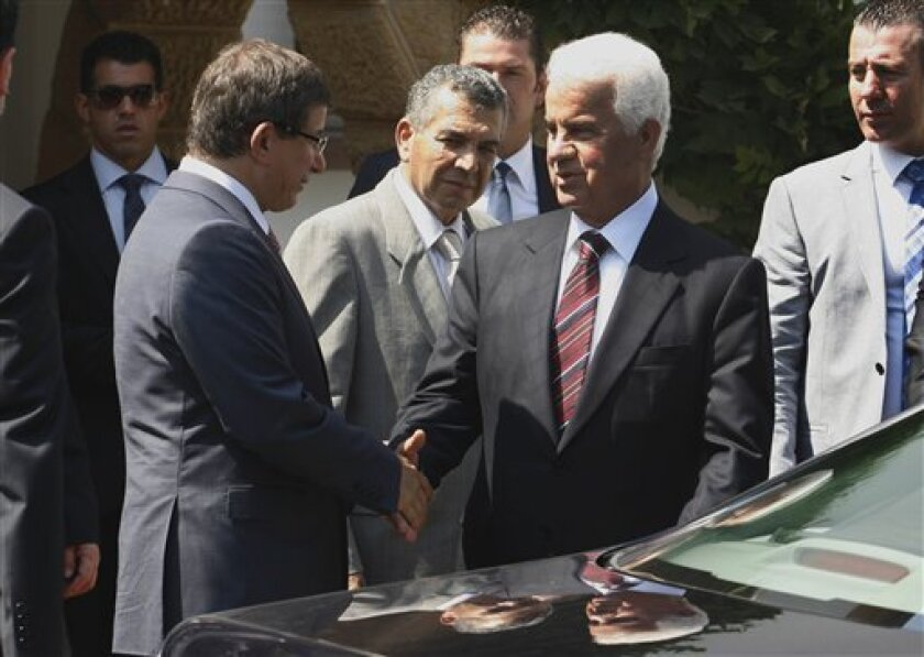 "Turkey's Foreign Minister Ahmet Davutoglu, left, shakes hands with Turkish Cypriot leader Dervis Eroglu, in the Turkish occupied area of the northern divided capital of Nicosia, Cyprus, Saturday, July 9, 2011. Turkey's foreign minister has called for a deal reunifying ethnically split Cyprus before the island assumes the European Union's presidency in mid-2012. Ahmet Davutoglu said Saturday that a ""new state"" reunifying Greek and Turkish Cypriots would make a Cyprus EU presidency legitimate because it would represent the whole island.(AP Photo/Philippos Christou)"