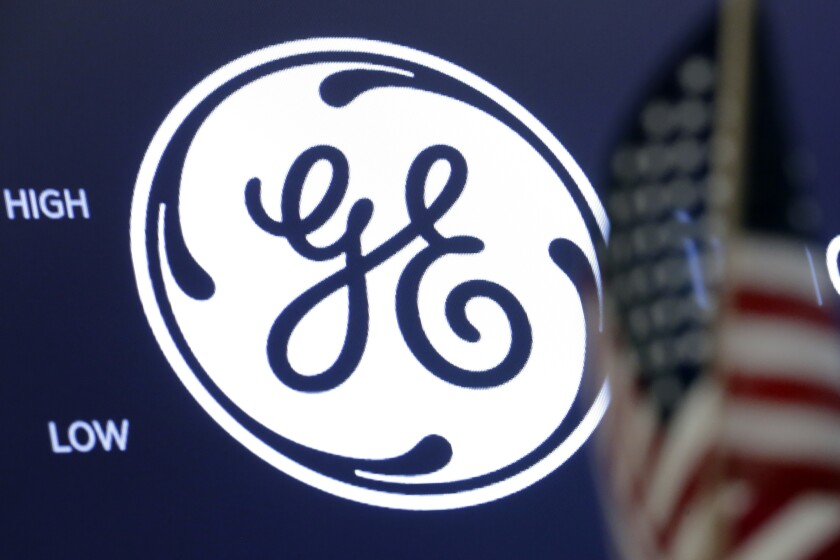 FILE - In this June 26, 2018, file photo the General Electric logo appears above a trading post on the floor of the New York Stock Exchange. Ireland's AerCap Holdings confirmed that it is in talks to buy General Electric's aircraft leasing business as the former industrial conglomerate continues to divest from the non-core businesses that nearly sank it during the 2008 financial crisis. (AP Photo/Richard Drew, File)