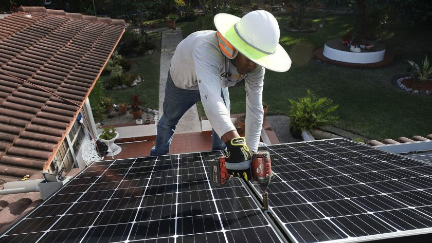 Roger Garbey of Goldin Solar installs a solar panel system on the roof of a home in Palmetto Bay, Fla., in January.