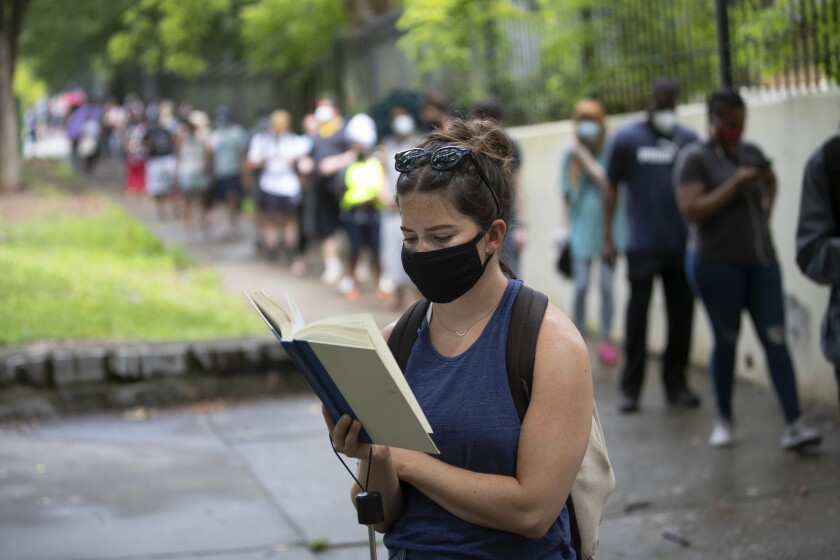 Kelsey Luker reads as she waits in line to vote Tuesday in Atlanta.