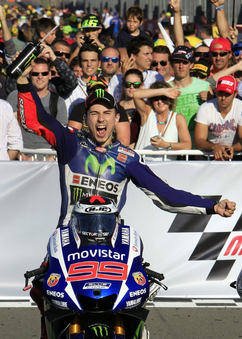 MotoGP rider Jorge Lorenzo of Spain celebrates after winning the race during the Valencia Motorcycle Grand Prix, the last race of the season, at the Ricardo Tormo circuit in Cheste near Valencia, Spain, Sunday, Nov. 8, 2015. (AP Photo/Alberto Saiz)