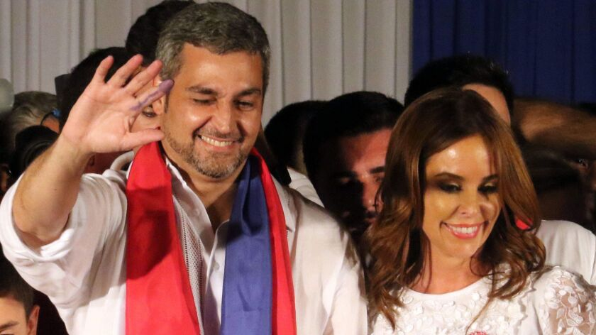 Mario Abdo Benitez reacts to his supporters, accompanied by his wife Silvana Lopez in front of the headquarters of the Colorado Party in Asuncion, Paraguay, on April 22.