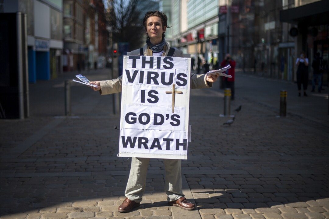 A man wears a religious placard on Market Street in Manchester, England.