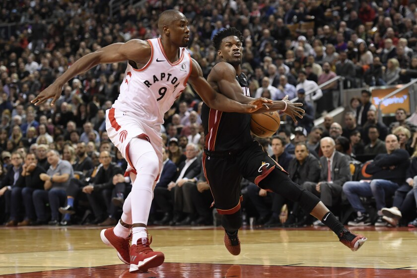 Miami Heat forward Jimmy Butler (22) drives past Toronto Raptors forward Serge Ibaka (9) during the second half of an NBA basketball game Tuesday, Dec. 3, 2019, in Toronto. (Nathan Denette/The Canadian Press via AP)