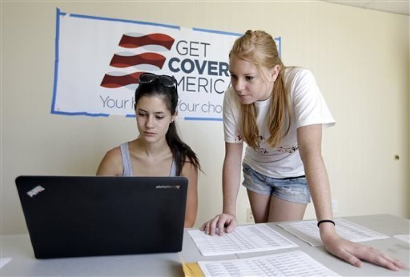 Ashley Hentze, left, of Lakeland, Fla., gets help signing up for health care from Kristen Nash, a volunteer with Enroll America, a private, non-profit organization running a grassroots campaign to encourage people to sign up for health care, Tuesday, Oct. 1, 2013, Tampa, Fla.