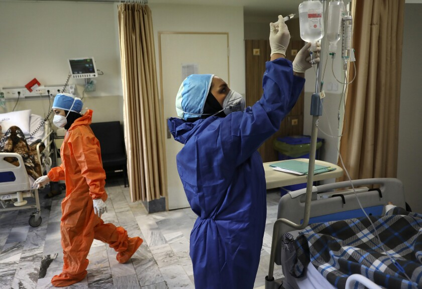 Nurses tend to COVID-19 patients in Tehran hospital in June
