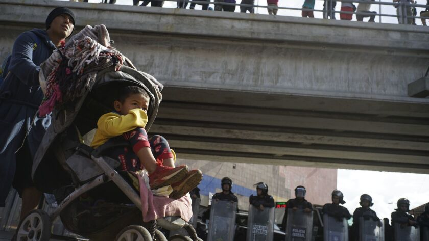 A migrant man pushes a child in a baby stroller past a cordon of riot police as he joins a small gro