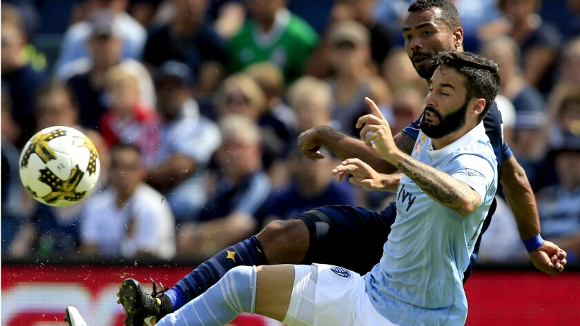 Sporting Kansas City forward Cristian Lobato plays the ball against Galaxy defender Ashley Cole, back, during a match Sept. 24, 2017.