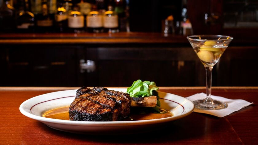 A bone-in ribeye steak with a martini at The Musso and Frank Grill.