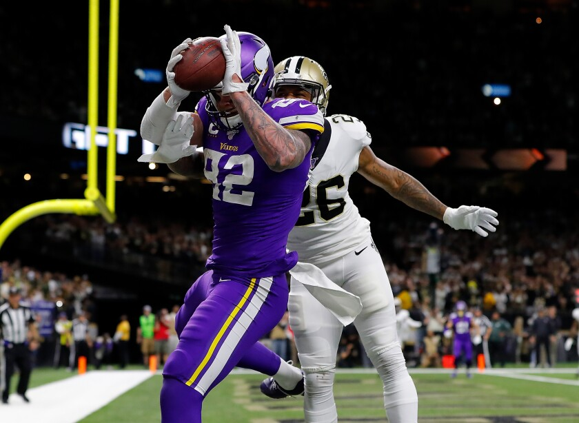 Kyle Rudolph of the Minnesota Vikings makes the winning touchdown reception against P.J. Williams of the New Orleans Saints during overtime in the NFC Wild Card Playoff game at Mercedes Benz Superdome on Sunday in New Orleans.