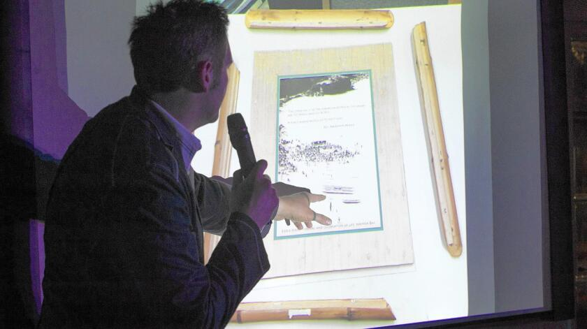 SyFy channel host Ben Hansen talks Wednesday night at the International Surfing Museum in Huntington Beach about a bamboo picture frame that was seen on security cameras mysteriously falling off its stand.
