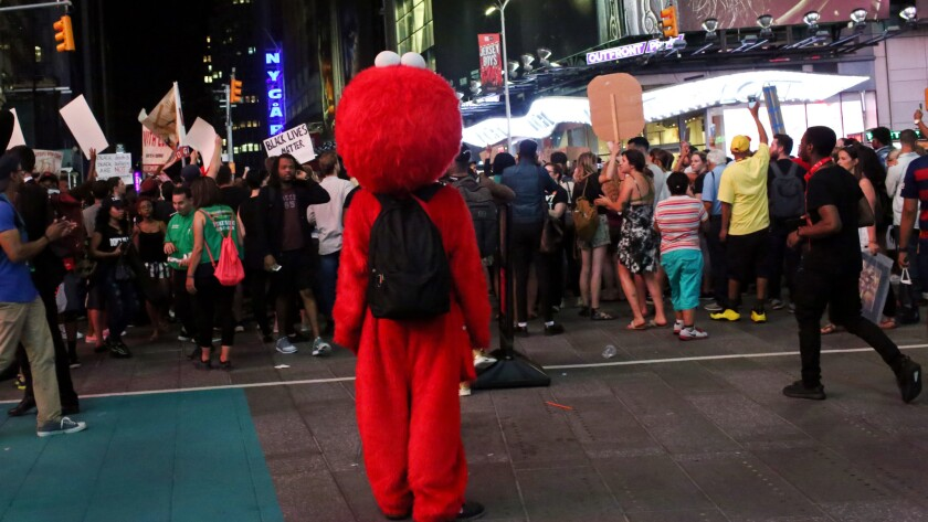 Costumed characters watch activists protest in Times Square.