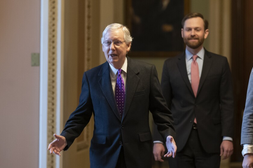 Senate Majority Leader Mitch McConnell of Kentucky, left, walks from the Senate floor on Capitol Hill on Tuesday.
