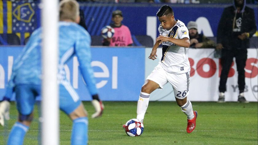 In this Saturday, March 2, 2019 photo, LA Galaxy midfielder Efrain Alvarez, right, prepares to kick