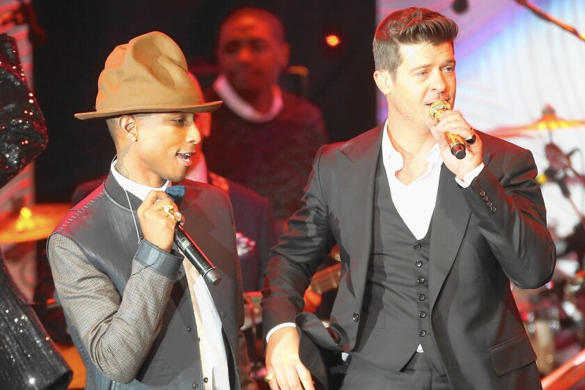 Recording artists Pharrell Williams, left, and Robin Thicke perform at the Beverly Hilton on Jan. 25, 2014.
