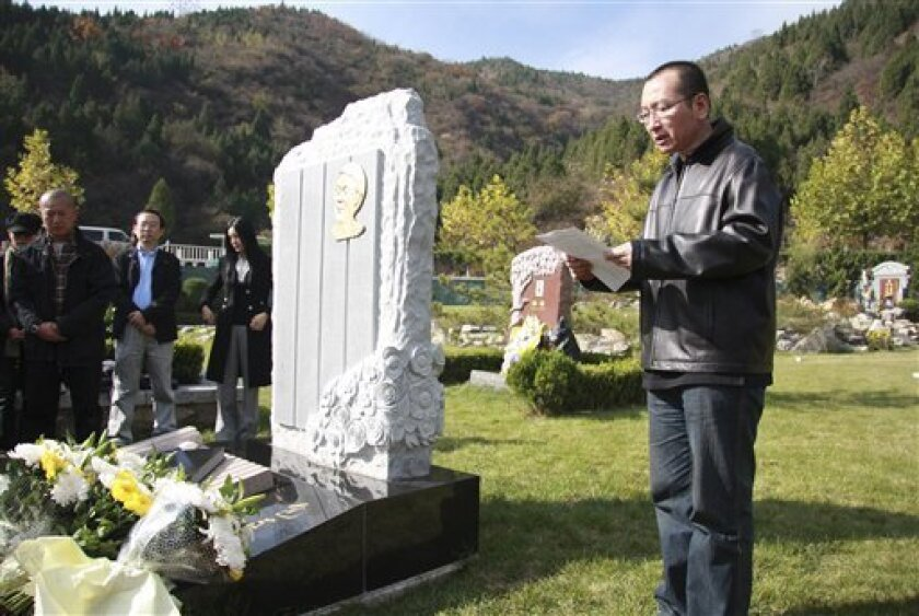 """This Oct. 28, 2008 photo shows Liu Xiaobo, right, reading a letter beside the grave of Bao Zunxin, a Chinese historian and political dissident who was arrested and jailed for his role in the 1989 Tiananmen Square democracy protests in Beijing, China. When the police came for Liu Xiaobo, China's best chance in decades to win the Nobel Peace Prize, they couldn't tell him why they were taking him away this time. The line in the detention order for """"motive"""" was blank. (AP Photo) NO SALES, CHINA OUT"""