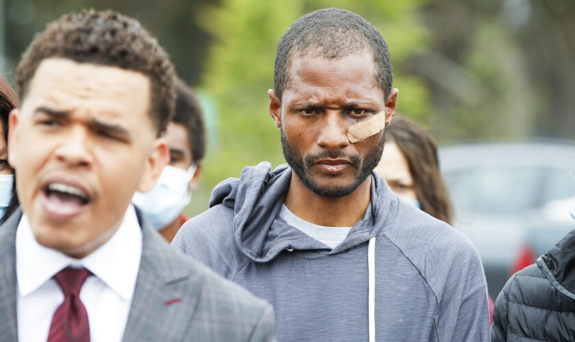 Jesse Evans, 34, appears at a May 14 news conference in La Jolla held by the Rev. Shane Harris (left).