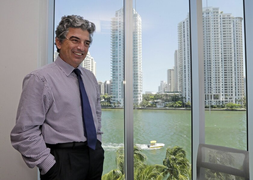 FILE - In this Wednesday, May 20, 2015, file photo, Carlos Rosso, president of the condominium division at The Related Group, poses for a photo at his office in Miami. Wealthy expats fleeing financial and political turmoil have poured their fortunes into glass and steel condo towers for years. The buying frenzy out of Brazil paused briefly this year, when its currency weakened in value against the dollar, but as the situation worsens in Brazil, real estate developers say sales are picking up again in Miami. (AP Photo/Alan Diaz, File)