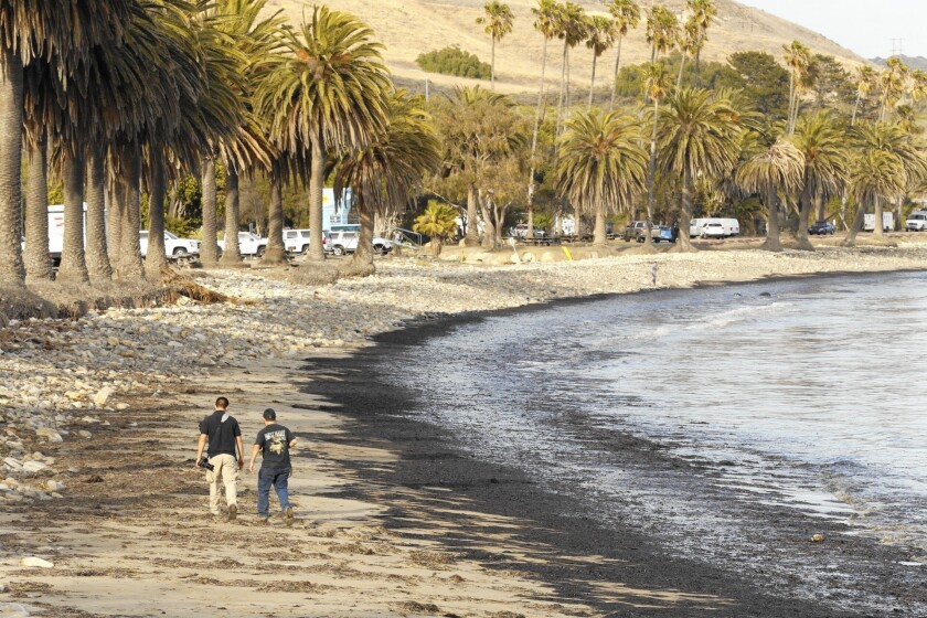 People stroll Refugio State Beach after it was coated with oil from a broken pipeline.