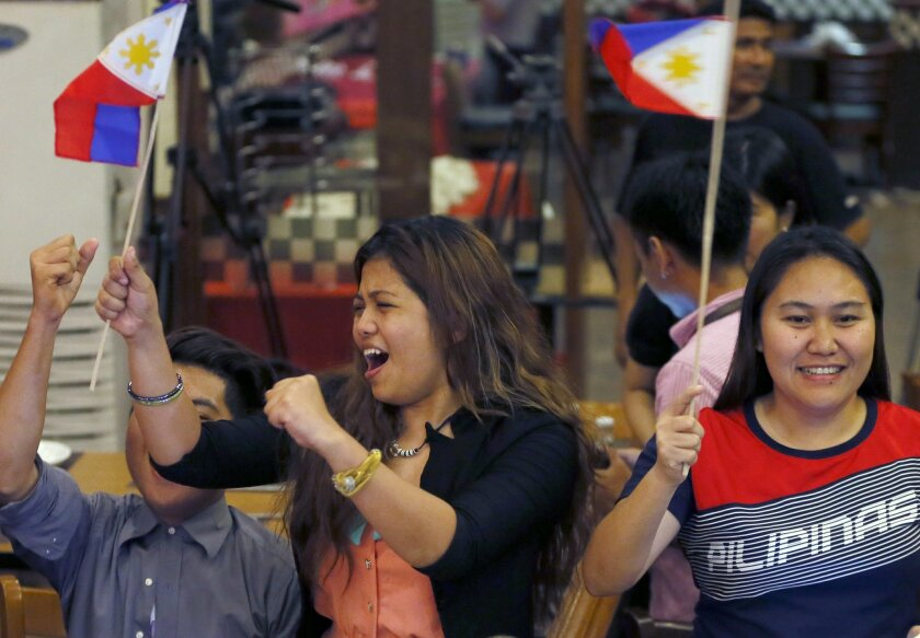 """Filipinos cheer moments after the Hague-based U.N. international arbitration tribunal ruled in favor of the Philippines in its case against China on the dispute in South China Sea Tuesday, July 12, 2016 in Manila, Philippines. The tribunal has found that there is no legal basis for China's """"nine-dash line"""" claiming rights to much of the South China Sea. The tribunal issued its ruling Tuesday in The Hague in response to an arbitration case brought by the Philippines against China. (AP Photo/Bullit Marquez)"""