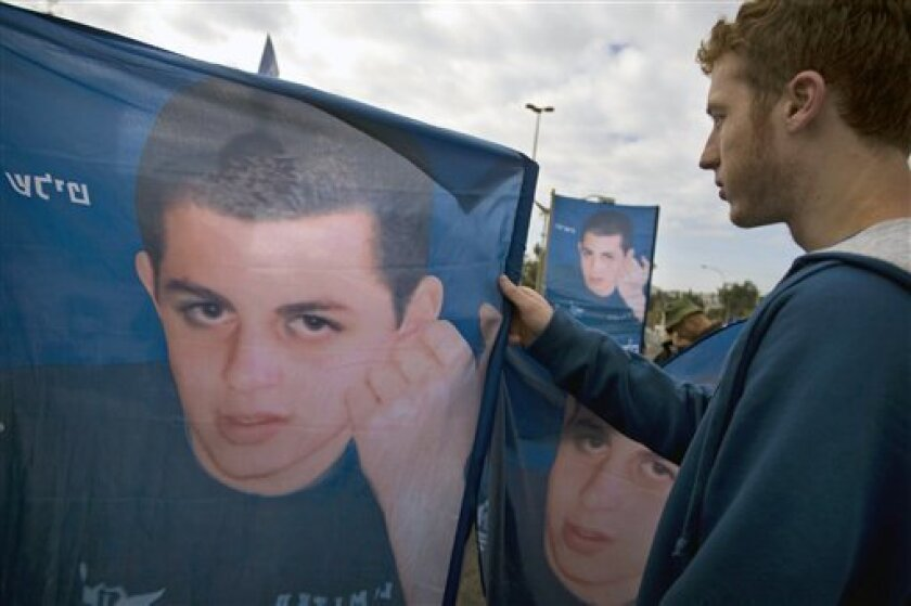 An Israeli demonstrator adjusts a banner showing Israeli soldier Sgt. Gilad Schalit who was captured by Hamas-allied militants in 2006, during a rally calling for his release outside the Prime Minister's office in Jerusalem, Wednesday, Feb. 18, 2009. Israel's Security Cabinet opened debate Wednesday on a possible prisoner exchange with Hamas which could trade hundreds of Palestinian prisoners for Schalit. (AP Photo/Sebastian Scheiner)