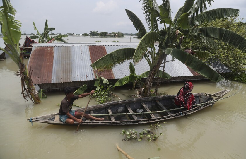 An Indian flood affected man and a woman ride on a country boat in Gagolmari village, Morigaon district, Assam, India, Tuesday, July 14, 2020. Hundreds of thousands of people have been affected by floodwaters and landslides following incessant rainfall in the region. (AP Photo/Anupam Nath)