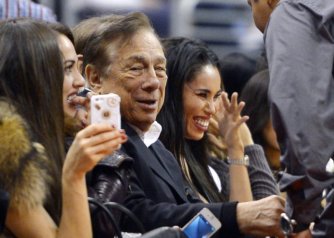 Los Angeles Clippers owner Donald Sterling, center, and V. Stiviano, right, watch the Clippers play the Sacramento Kings at Staples Center.
