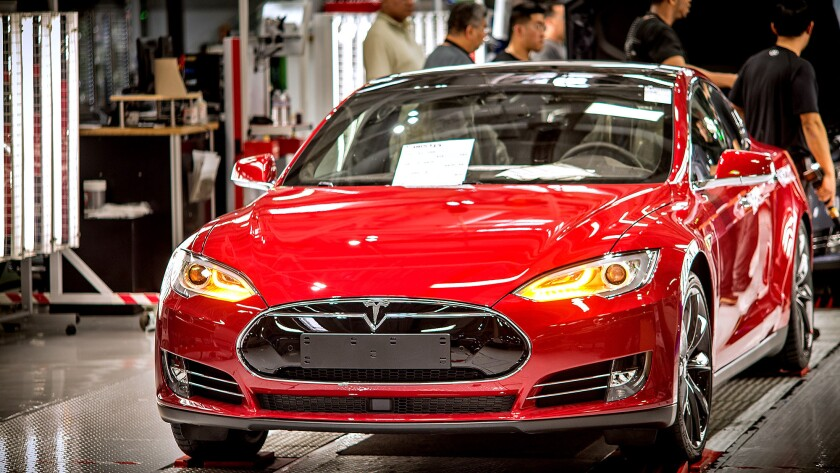 A Telsa car is readied for the final stages of preparation before being released from the assembly line at Tesla's factory in Fremont.