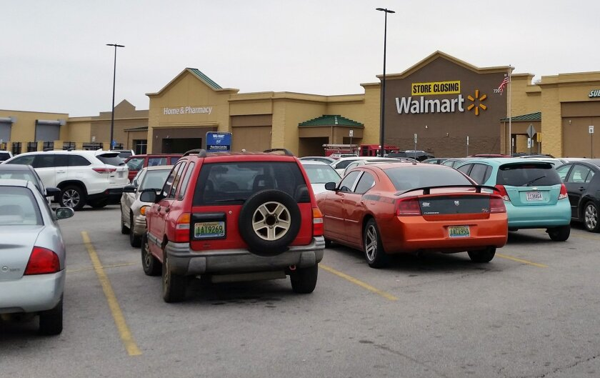In this photo taken Thursday, Jan. 21, 2016, cars fill the parking lot of a Wal-Mart store in Fairfield, Ala., as it prepared to shut down. Stores slated to shut down Thursday, Jan. 28, 2016, will leave residents in parts of Fairfield, Ala.; Coal Hill, Ark.; and Wichita, Kan., without a supermarket. (AP Photo/Phillip Lucas)