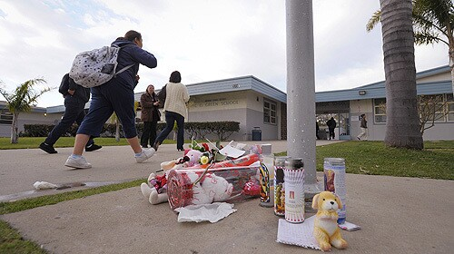 Students pass by a makeshift memorial honoring fifteen-year-old Lawrence King which lies beneath the flagpole at E.O. Green School Thursday, Feb. 14, 2008.