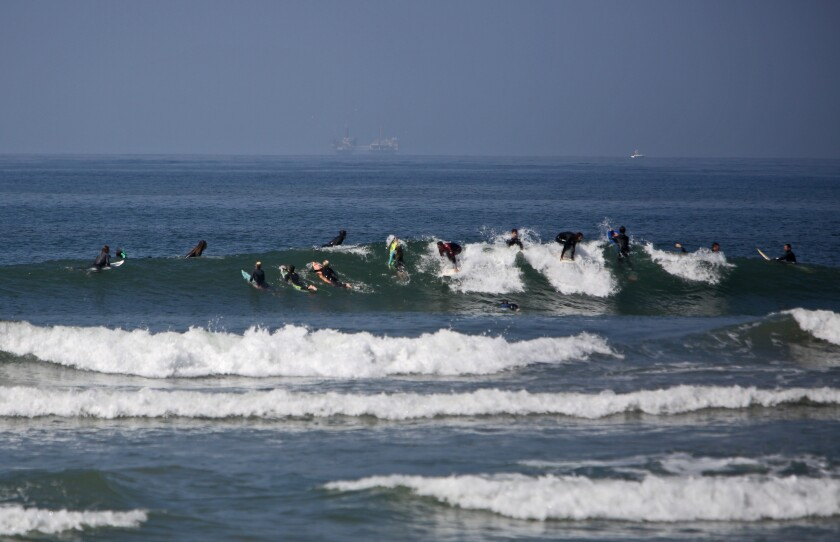 There were dozens of surfers who took to the waves next to the pier in Huntington Beach on May 2, despite a state closure order..