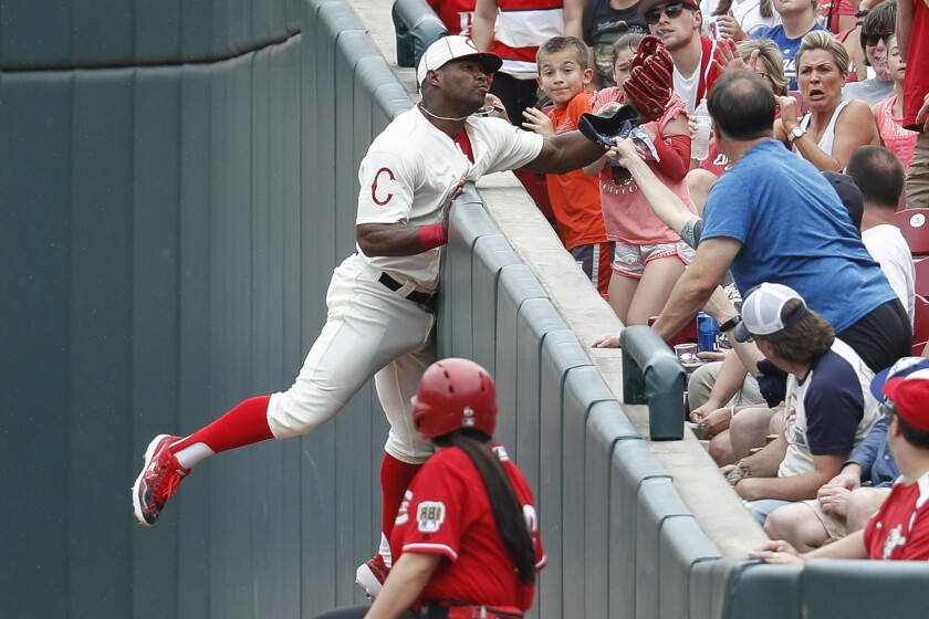 Cincinnati Reds' Yasiel Puig catches a foul ball hit by Los Angeles Dodgers' Hyun-Jin Ryu.