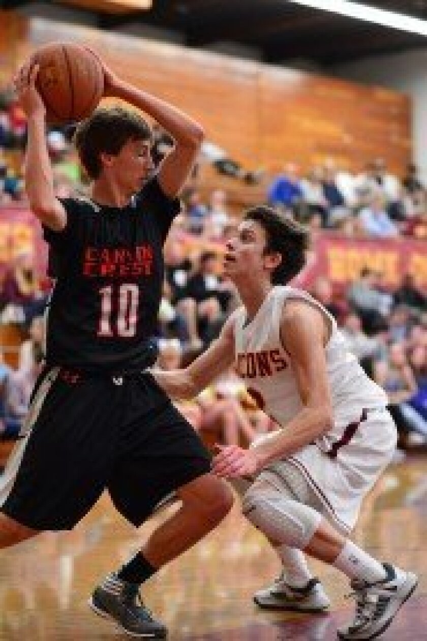 Torrey Pines' Zack Wagner defends against CCA's Aaron Schrock in a Feb. 15 matchup. Torrey Pines won 62-53. Photo/Anna Scipione