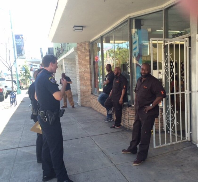 Officers talk to barbers outside the 619 Barber Shop