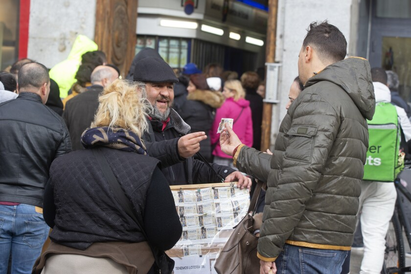 A man buys a Christmas lottery ticket from a street seller in Madrid, Spain, Saturday, Dec. 21, 2019. Spain's bumper Christmas lottery draw known as El Gordo, or The Fat One, will be held on Dec. 22. (AP Photo/Paul White)