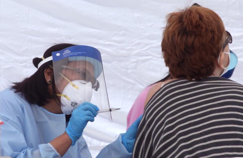 A nurse gives a woman a COVID-19 vaccine