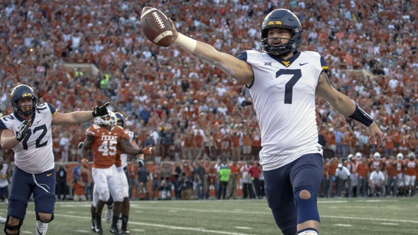 FILE - In this Nov. 3, 2018, file photo, West Virginia quarterback Will Grier (7) scores the game-wi