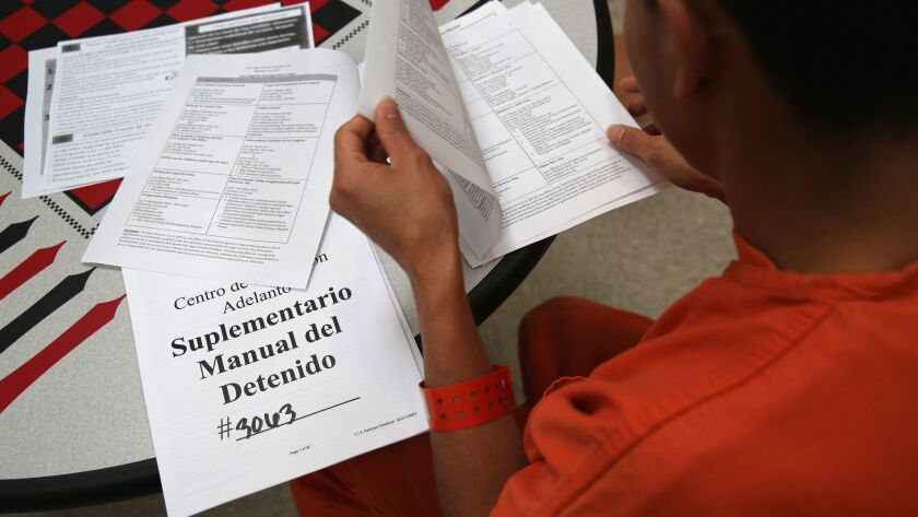 An immigrant detainee reads through paperwork in a general population block at the Adelanto Detention Facility in Adelanto, Calif. The facility is managed by the private GEO Group.