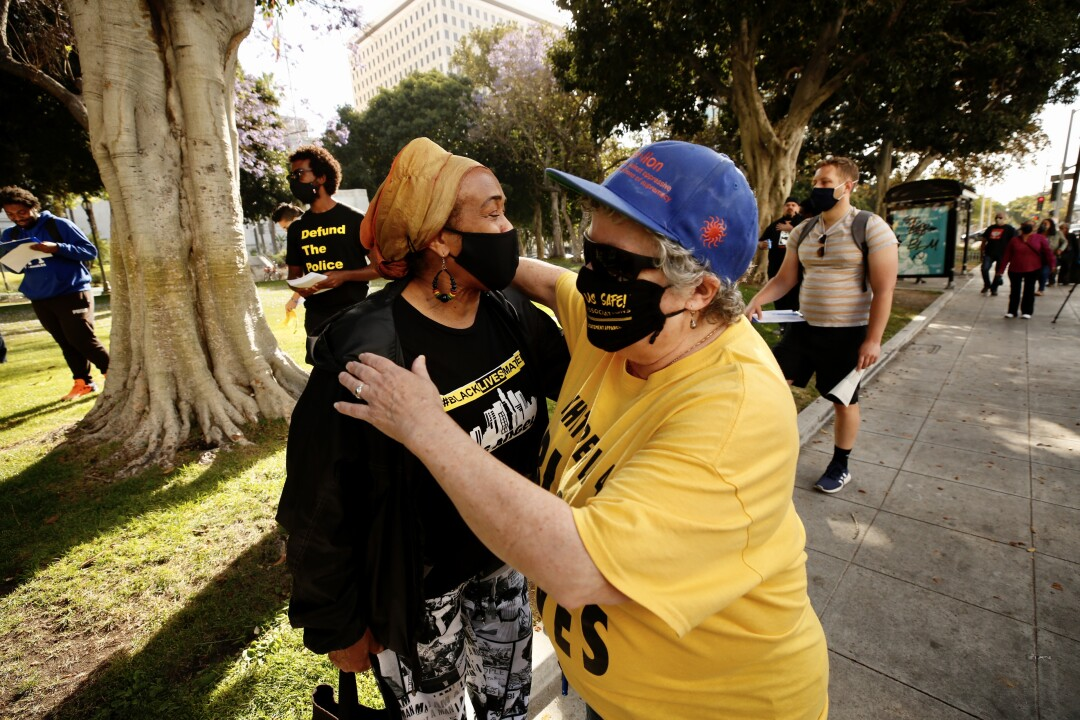 Audrey Georg, right, hugs Paula Minor, before a rally at city hall in downtown Los Angeles Tuesday.