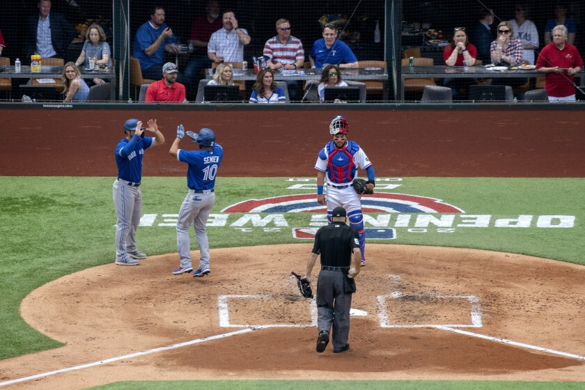 Toronto Blue Jays' Marcus Semien (10) is congratulated by Randal Grichuk after hitting a two-run home run, which scored Grichuk, as Texas Rangers catcher Jose Trevino and home plate umpire Jansen Visconti look on during the second inning of a baseball game Monday, April 5, 2021, in Arlington, Texas. (AP Photo/Jeffrey McWhorter)