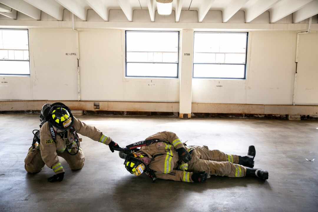 "Recruit Jonathan Howarth attempts a ""victim drag"" on fellow recruit Michael Brown as they learn how to save their fellow firefighters in a mayday situation. ""'Aint nobody else is going to come for us,"" their instructor Alex Wallbrett yells. ""We're it. We're the last line of defense. I mean, maybe you could call a cop and a cop could come running in to come save you but that's going to be kind of embarrassing."""