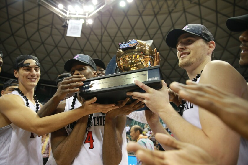 SDSU players hold the championship trophy from the Diamond Head Classic in Honolulu on Christmas Day.