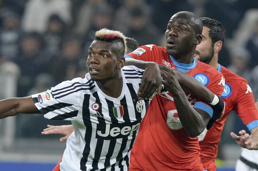 Juventus' Paul Pogba challenges the ball with Napoli's Kalidou Koulibaly during a Serie A soccer match between Juventus and Napoli at the Juventus stadium, in Turin, Italy, Saturday, Feb. 13, 2016. (AP Photo/Massimo Pinca)