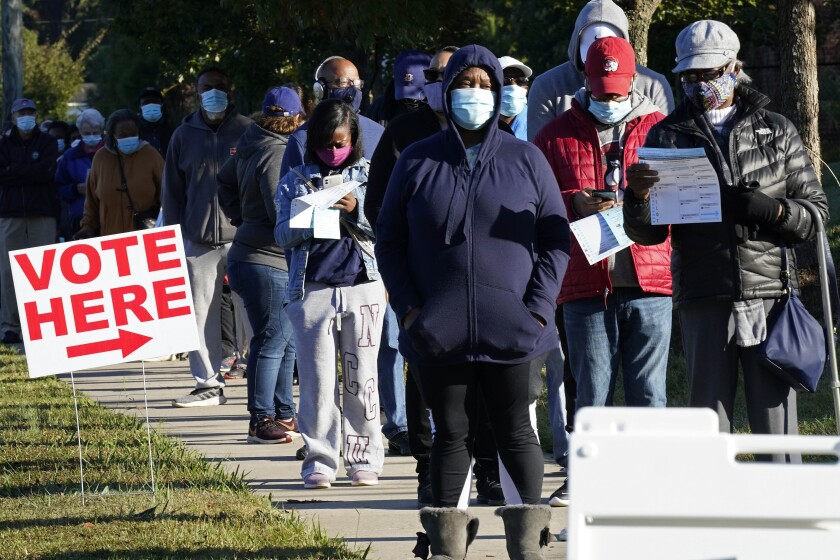 Early voters line up to cast their ballots at the South Regional Library polling location in Durham, N.C., Thursday, Oct. 15, 2020. (AP Photo/Gerry Broome)