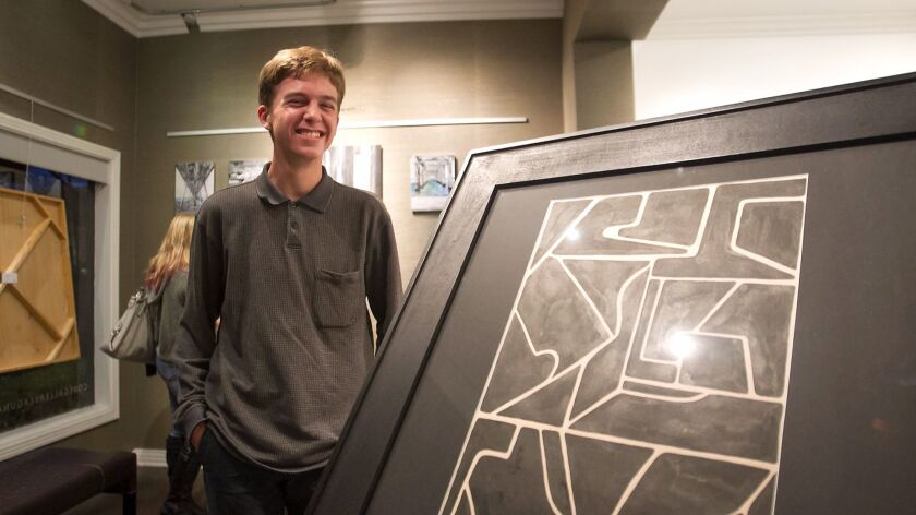"""Laguna Beach High student Zander Raymond stands next to his ink on paper piece """"Shape Study"""" at the Cove Gallery during Thursday's Art Walk. The gallery and high school partnered on a program that allows two artists at a time to display their work."""