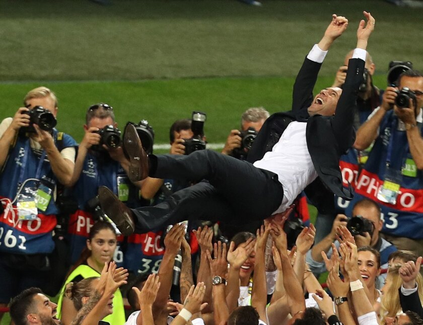 Real Madrid's head coach Zinedine Zidane is thrown into the air in celebration after the Champions League final soccer match between Real Madrid and Atletico Madrid at the San Siro stadium in Milan, Italy, Saturday, May 28, 2016. Real Madrid won 5-4 on penalties after the match ended 1-1 after extr