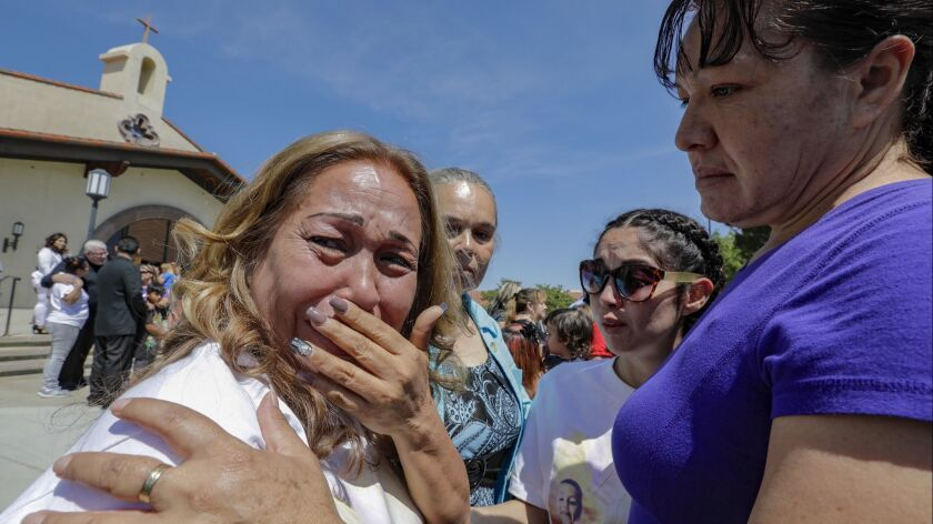 Concepcion Ramirez, left, grandmother of 10-year-old Anthony Avalos, weeps at the end of funeral services held at Saint Junipero Serra Parish in Quartz Hills.
