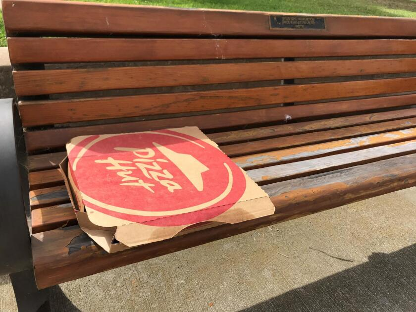 Pizza-box trash is seen on a bench in front of the La Jolla Recreation Center.